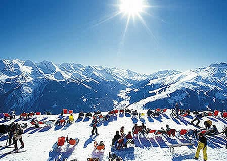 Winter sun-bath. Skiers bathing in the sun's infrared.